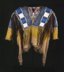 Chemise cérémonielle ayant appartenu au chef Red Cloud, Oglada Lakota. Ces chemises, portées lors de grandes occasions, étaient l'attribut des hommes importants. Brodée de bandes de perles de verres, elle est ornée de cheveux humains (soit des scalps pris à l'ennemi, soit des mèches offertes par les membres de la famille du guerrier), le bleu symbolise le ciel et le jaune la terre. La partie centrale indiquait la position sociale du porteur. Chez les Sioux, ils étaient six ou sept par tribu : un chef de guerre, un gestionnaire des problèmes internes, un chargé des relations avec les Européens… © Buffalo Bill Center of the West, Cody, Wyoming, USA, Adolf Spohr Collection, don de Larry Sheerin. Inv. NA.202.598.