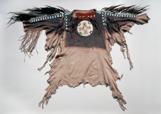 Chemise (poncho à manches) d'homme, vers 1830, artiste des Plaines du Nord, probablement Blackfeet. Reflétant la vision du monde des chasseurs amérindiens, cette chemise, dans le respect de la forme des peaux utilisées, cherche à préserver l'identité et la puissance spirituelle de l'animal. Plus qu'un vêtement de protection contre le mauvais temps, il s'agirait de tenues de cérémonie réservées aux chefs et aux guerriers d'exception. Les larges rosettes en piquants de porc-épic sur le devant et le dos représentent le Soleil et la Lune et rappellent les cercles peints sur la poitrine des guerriers et des hommes en quête de vision. Le motif en croix figure l'Étoile du Matin, fils du Soleil et de la Lune. La griffe est un ajout personnel, signe de puissance. Quant à la frange de cheveux, il s'agissait d'un don que faisaient les membres d'une communauté. Peaux d'antilope ou de mouflon, broderie de piquants de porc-épic, perles de verre, pigment, crin de cheval, boucles de scalp, tendons et griffe de grizzli. Dim. : 100 x 70 cm. © Bernisches Historiches Museum, Berne, Suisse, coll. L. A. Schoch, Inv. 1890.410.7.