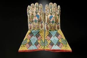 Paire de gantelets, Sioux-Métis, Dakota du Nord ou du Sud, vers 1890. Les Indiens avaient découvert les gantelets par l'entremise des soldats de la cavalerie américaine, dans les années 1870. Éclatants de couleur, chaque manchette est ornée d'une croix formée de quatre drapeaux. Le décor floral abstrait est caractéristique du perlage des Sioux à la fin du XIXe siècle. Peau tannée, perles de verre et de laiton, tissu en coton. Dim. : 36,7 x 20 cm. © The Hirschfield Family Collection, Courtesy of Berte and Alan Hirschfield.