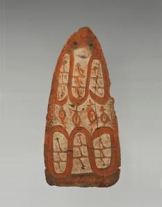 Bouclier de guerre, Asmat, Irian Jaya, Nouvelle-Guinée occidentale (sous souveraineté indonésienne). Pour les guerriers Asmat, le bouclier était un des accessoires les plus symboliques et les plus puissants. À la fois objet fonctionnel pour se protéger des lances et des flèches des ennemies, ils représentaient également une protection surnaturelle à travers les motifs ornant sa surface. Cet exemplaire est orné de roussettes tar. La tête ronde, à l'extrémité, est une raie pastenague puru. Bois et pigments. H. : 116,4 cm. Offert par le Père Le Cocq d'Armandville en 1929 aux MRAH. Acquis des MRAH par voie d'échange en 1979. © MRAC. Inv. EO.1979.1.1255.