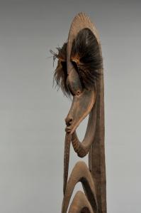 Charme de chasse anthropomorphe (détail), Alamblak, rivière Karawari, cours moyen du fleuve Sepik. Dénommés yipwon, ils étaient invoqués dans la préparation des expéditions guerrières. Chaque homme en possédait plusieurs, hérités de ses ancêtres ou sculptés par lui-même. De différentes tailles, ces figures sont toujours composées d'une large tête surmontant un corps squelettique et, parfois, d'un pied. L'arc sommital évoquerait une coiffure et l'arc sous le menton un bras. Le corps se compose d'une série de crochets représentant les côtes du personnage. Ces sculptures représentent des ancêtres mythiques qui étaient associés à la chasse et à la guerre. Les exemplaires de grande taille étaient la propriété d'un groupe familial ou d'un clan. Conservées dans la maison des hommes, seuls les initiés pouvaient les contempler. Avant de partir à la chasse ou à la guerre, elles étaient activées par une offrande de nourriture ou enduites d'une substance à laquelle était attribuée un pouvoir particulier. Bois, plumes de casoar et pigments. H. : 189,2 cm. Acquis par voie d'échange avant 1970. © MRAC. Inv. EO.1970.89.4.