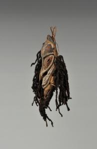 Masquette, région du bas Sepik. Par sa dimension, ce petit masque avait probablement un usage domestique. Ils étaient souvent fixés à un sac ou à un objet personnel ou encore utilisé comme ornement de coiffure ou encore comme pectoral. La présence de cheveux humains indique qu'il était chargé d'une grande puissance. Bois, cheveux humains, fibre, rotin et pigments. H. : 21,2 cm. Offert par Henri Lavachery, en 1932, aux MRAH. Acquis des MRAH par voie d'échange en 1979. © MRAC. Inv. EO.1979.1.1297.