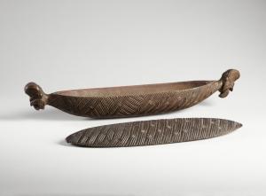 Boîte à plumes, Maori, côte est de l'île nord (baie de Plenty), Nouvelle-Zélande (objet non exposé). Milieu du XIXe siècle. Chaque extrémité est ornée d'un visage expressif sculpté en ronde bosse. Les côtés et le couvercle sont couverts d'un motif d'entrelacs et de petites lignes transversales. Les pendentifs de jade et les plumes de l'oiseau « huia », dont les Maori se servaient pour orner leurs manteaux, étaient conservés dans ces boîtes. Ces coffrets pouvaient être suspendus aux chevrons de la case par les excroissances sculptées à leurs extrémités. La forme oblongue rappelle celle des pirogues et renvoie aux mythes d'arrivée des premiers clans maoris par pirogue. Bois. L. : 56. © Musée du quai Branly, 71.1885.52.96.1-2. Photo : Claude Germain.