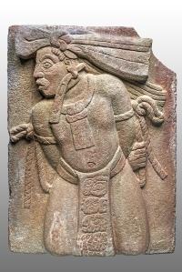 Haut-relief en grès montrant un captif, la bande de toile ou de papier pendue à son oreille indique son sacrifice imminent. Son pagne porte l'inscription de son nom et de son origine, ainsi que celui de son vainqueur. Début du VIIIe siècle. Classique récent (600-800 ap. J.-C.). Monument 154 de Toniná, Chiapas, Mexique. © Museo Nacional de Antropología, Mexico. Photo : I. Guevara. Réf. : Maya-NCH-3090.