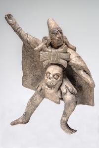Statuette en terre cuite représentant un dignitaire-guerrier-chaman portant un crâne attaché à sa ceinture, prononçant un discours ou exécutant un rite de danse. Jaina, Campeche, Mexique. Classique récent (600-800 ap. J.-C.). Dim. : 13 x 11 cm. © Museo Nacional de Antropología, Mexico. Coll. Stavenhagen. Réf. : Maya-NCH-1008. Photo : I. Guevara.