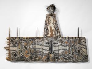 Frise porte-crânes avec crâne surmodelé, Iatmul, province de l'est du Sepik, Papouasie Nouvelle-Guinée. Pétiole de sagoutier, fibres, rotin, pigments, crâne surmodelé et plumes. L. : 180 cm. H. : 84 cm. © Musée du quai Branly, Inv. 72.1964.11.9.1. Photo C. Germain.