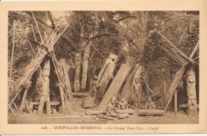 """« 108. - Nouvelles-Hébrides. - Un grand tam-tam à Ouala [Ouala ou Wala ou encore Valla se situe au large de la côte nord-est de Malekula]. E. B. » 9 x 14,1 cm. Il s'agit d'une place de danse où se dresse un """"orchestre"""" de tambours à fente devant un monument de grade et entre deux cases pour cochons de grade ¬ ¬— au Vanuatu, les cochons gravissent eux aussi des grades, au moment où les dents des maxillaires inférieurs, recourbées, achèvent leur premier tour —, abritant chacune un poteau sculpté, devant une table en pierre, l'abri étant surmonté d'une sculpture faîtière représentant un oiseau aux ailes déployées. Au centre et à droite de cette photographie, on aperçoit, suspendue à un de ces tambours, une série de mâchoires inférieures de porcs, marques de la valeur des bêtes qui ont été payées pour son acquisition. Au premier plan, des indigènes assis devant de petits tambours musicaux."""