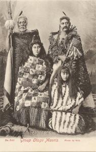« No. 340 Group Otago Maoris. Photo by Gill. F. T. Series ». 13,9 x 8,8 cm. L'auteur de cette photographie de studio est Henry John Gill. Les Maori étaient passés maître dans l'art de la trame torsadée pour la fabrication de larges capes destinées aux chefs et aux personnages de haut rang — utilisant le lin, les poils de chien et les plumes d'oiseaux, dont le kiwi —, en particulier, pour se protéger de la pluie, comme on peut le voir sur cette carte postale où divers modèles drapent ces quatre personnages. Celui de droite porte un pendentif d'oreille kawakawa en néphrite et une arme tewhatewha tandis que celui de gauche s'appui sur un taiaha.