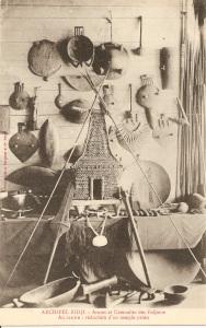 « Archipel Fidji. – Armes et ustensiles des Fidjiens. Au centre : réduction d'un temple païen ». Phototypie A. Bergeret et Cie. Nancy. 14,1 x 8,9 cm. Casse-tête, lances, appuis-nuque, ornements plats et coupes et, au centre, un modèle de temple ou autel portable bure kalou en fibres de coco tressées.