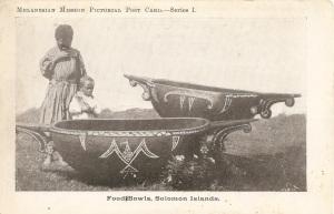 « Food Bowls, Solomon Islands. Melanesian Mission Pictorial Post Card.—Series I. ». 9 x 13,8 cm. Les sculpteurs de Santa Calina étaient renommés pour leurs bols en bois incrustés de coquillages. Ces deux grands exemplaires sont des bols de fêtes utilisés pour une préparation à base de purée de taro appelée sugusugu. La plus importante de ces fêtes était le maraufu ou rite d'initiation des jeunes garçons.