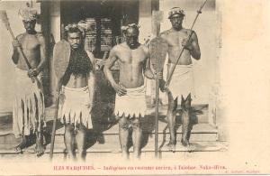 « Îles Marquises. — Indigènes en costume ancien, à Taiohae, Nuka-Hiva. A. Itchner, Huahine. ». 8,8 x 13,7 cm. Au centre les deux personnages sont coiffés d'une couronne hei kohio ou peue'ei ou peue'koi'o et tiennent des pagaies hoe. Celui de gauche porte un casque en peau de poisson porc-épic (Diodon holocanthus) tel qu'on en trouvait aux îles Gilbert (Kiribati) tandis que celui de droite est orné d'une couronne paekaha, et tiennent des massues u'u.