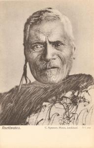 « Ruetiwatea [ou Rueti Watea]. C. Spencer, Photo, Auckland. No. 102. ». 13,7 x 8,7 cm. Cette photographie a été prise par Charles Spencer en 1912. Ce chef non identifié de l'iwi Te Ati Hau a Paparangi, région de la rivière Wanganui, porte une cape korowai et un pendentif d'oreille en jade à l'oreille droite. Probablement originaire de la région de la rivière Wanganui, au sud-ouest de l'île du Nord, les moko (tatouages) de son front et de son nez sont inhabituels.
