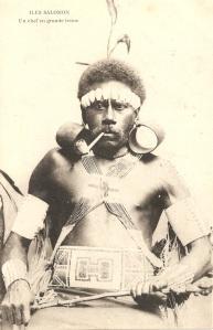 """« Îles Salomon. Un chef en grande tenue ». 14 x 8,9 cm. Portrait en buste d'un salomonais fumant la pipe. Plumes dans les cheveux, portant de larges boucles d'oreille en écaille de tortue ta'ota'ofunu, un ornement pectoral torisusu, en """"bandoulières croisées"""", une ceinture fo'o'aba, des brassards et des bracelets abagwaro constitués de perles de verre et un bandeau en coquillages composent la riche parure de ce chef."""