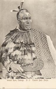 """« Wetani Rore, Tatangi. N. Z. Tourist Dept. Photo. F. T. Series No. 189. ». 13,9 x 8 ,8 cm. Ce chef de l'iwi Ngati Maniapoto et Ngati Kahungunu, région de Waikato-Waitomo, au visage tatoué porte une cape avec une large bordure taniko et des plumes dans ses cheveux. Les courtes lignes tatouées sur le haut de son front indiqueraient qu'il était """"maître d'armes"""". L'Auckland War Memorial Museum Library (Catalogue GN672.2 T2) possède une photographie (vers 1870), similaire à celle utilisée pour cette carte postale, attribuée au photographe George Pulman, spécialisé dans les portraits maori."""