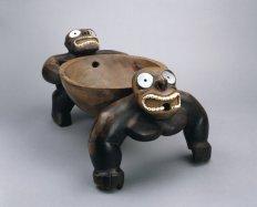 Bol à kava supporté par deux personnages, Hawaii, XVIIIe siècle. Bois, nacre et dents de sanglier. L. : 46,5 cm. Collecté lors du troisième voyage de Cook (1776-1780). © Trustees of the British Museum, Londres. Inv. HAW 46.