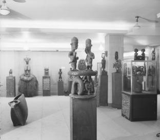 Vue de l'exposition d'art africain et océanien à la galerie du théâtre Pigalle, Paris, 1930. Au premier plan, tabouret Bamiléké, Cameroun (ex-coll. Pierre Loeb). © Société française de photographie (SFP) - Droits réservés.